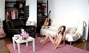 Молоденькая девушка сидит на полу голой и мастурбирует клитор