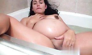 Дамочка на сносях принимает ванну и ласкает свою лысую пилотку